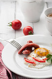 scrambled eggs on a plate with pieces of tomato and sausage