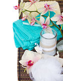 spa setting with blue towels, aroma candle and bath accessories