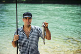 man fishing on river and showing fish to the camera