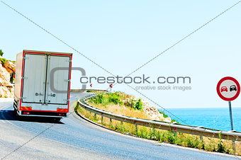 truck on a dangerous road along the sea