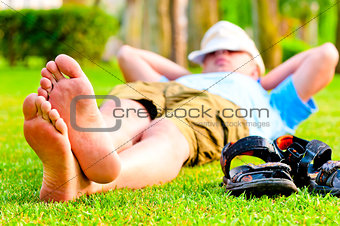 barefoot man is resting on the green grass