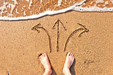 men's bare feet in the sand and arrows
