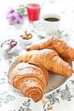 Croissants on table with jam, orange juice and coffee