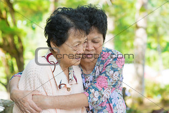 Asian mature woman hugs and consoling her crying old mother