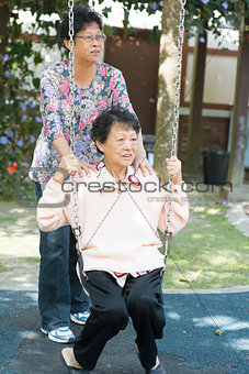 Asian senior women playing swing at outdoor garden park