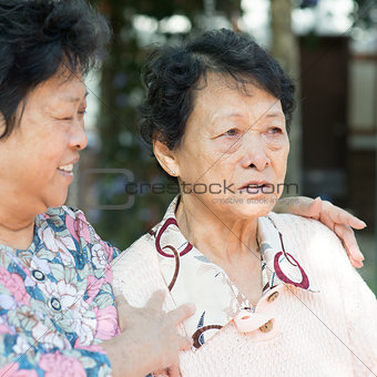 Mature woman consoling her crying old mother