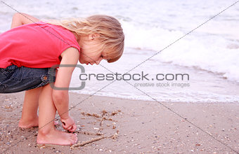 Little girl draws a sun in the sand on the beach