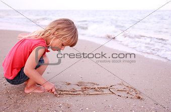 Little girl draws  in the sand on the beach