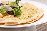 garlic pita bread pizza with salad on top