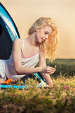 Beautiful blond woman camping