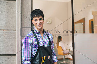 portrait of man working as hairdresser and smiling