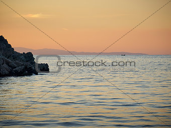 sea, rock and distant fishermen