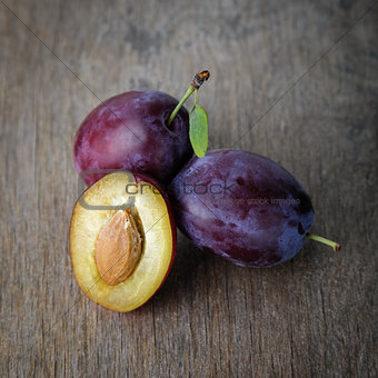 three ripe plums with leaves