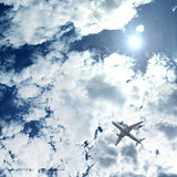 an airplane flying above blue clouds