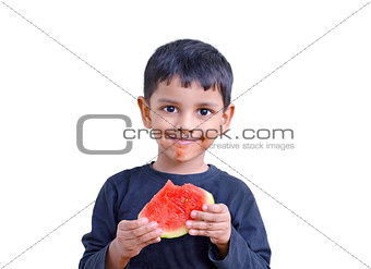3 year south Asian boy enjoying eating watermelon