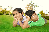 Cheerful south Asian boy and girl in a lawn