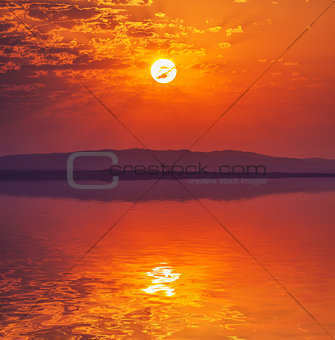Vibrant rising sun at dawn over water