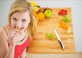 Portrait of happy young woman having a bite while cutting salad