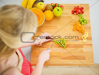 Portrait of young woman making fruits salad