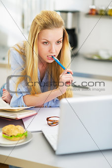 Thoughtful teenager girl studying in kitchen