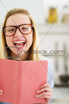Portrait of happy teenager girl with book in kitchen