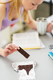 Closeup on teenager girl eating chocolate while studying in kitc