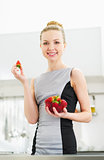 Young housewife eating strawberry in modern kitchen