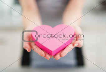 Closeup on heart in hand of young woman