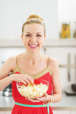Smiling young woman eating popcorn in kitchen