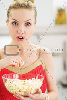 Portrait of young woman eating popcorn