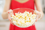 Closeup on plate with popcorn in hand of young woman