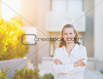 Portrait of smiling young woman standing in front of house build