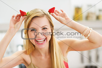 Smiling young woman making horns with strawberries