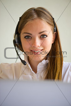 portrait of the girl of the operator with a font and the laptop