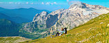 Woman Hiker Traveller in Mountains relaxing on grass with backpack rocky peaks on background Tourism concept High resolution Panoramic Landscape