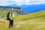 Woman Hiker with Backpack standing Outdoor on green Valley Grass and Mountains rocks on background Summer Day