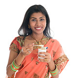 Traditional Indian woman eating yogurt