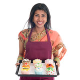 Traditional Indian woman baking bread and cupcakes