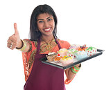 Thumb up Indian woman baking cupcakes