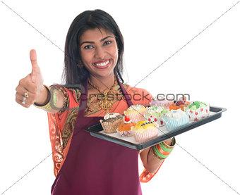 Thumb up Indian woman baking cupcakes