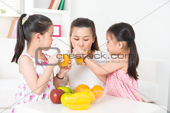 Asian parent and children drinking orange juice