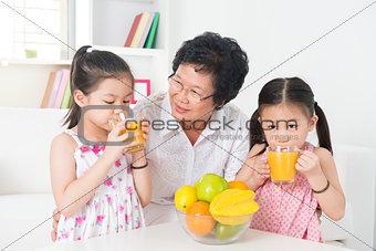 Asian children drinking orange juice
