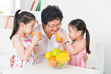 Asian family drinking fresh orange juice