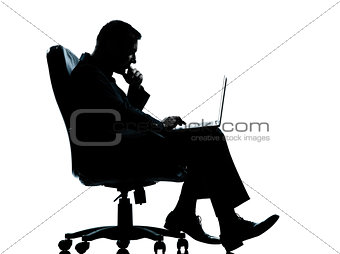 one business man computer computing sitting in armchair silhouet