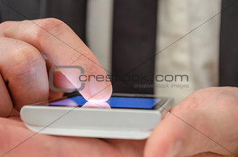 Finger of a businessman pointing at touch screen