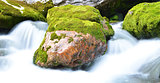 Long exposure image of a mountain stream flowing trough stone.