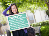 Mixed Race Female Student Holding Chalkboard With Theory and Def