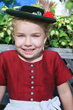 Portrait of a little smiling Bavarian girl with hat
