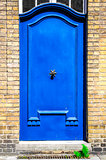 Blue entrance door in brick wall