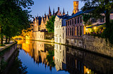 Water canal, medieval houses and bell tower at night in Bruges